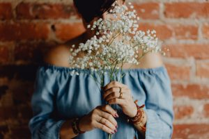A woman in a blue dress holds a branch of baby's breath. She can take a breath from wedding planning.