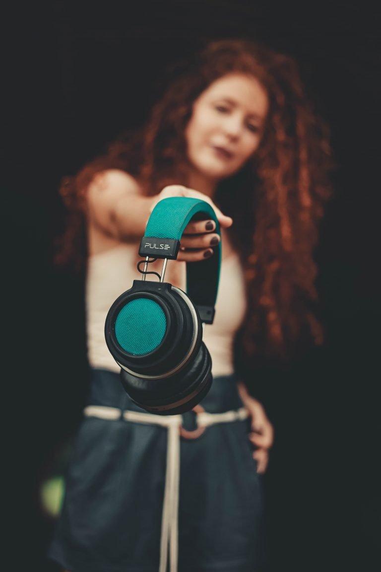 Girl handing headphones to you