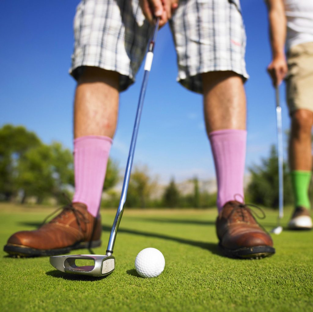 Pink socks, brown shoes, and plaid shorts. Getting ready for a putt.